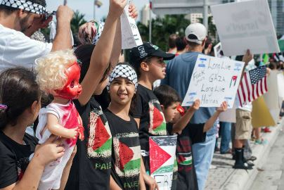 """During a protest, a young demonstrator holds sign saying 'F*ck Jews,' 'Long Live Gaza,' 'Long Live Hamas.'"""